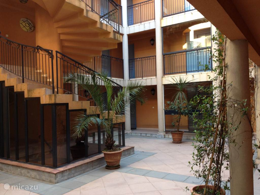 Binnenplaats vanwaar het appartement is te bereiken via de wenteltrap of de lift.