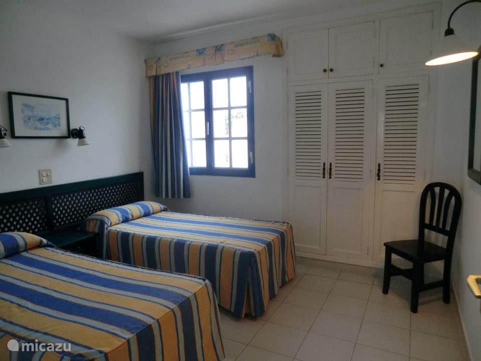 Een keurige slaapkamer met 2 bedden en een grote kast.