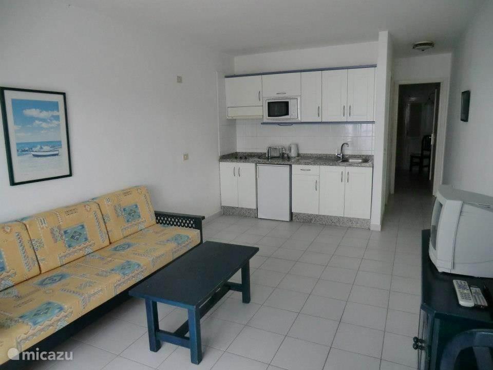 De woonkamer met slaapbank en open keuken.