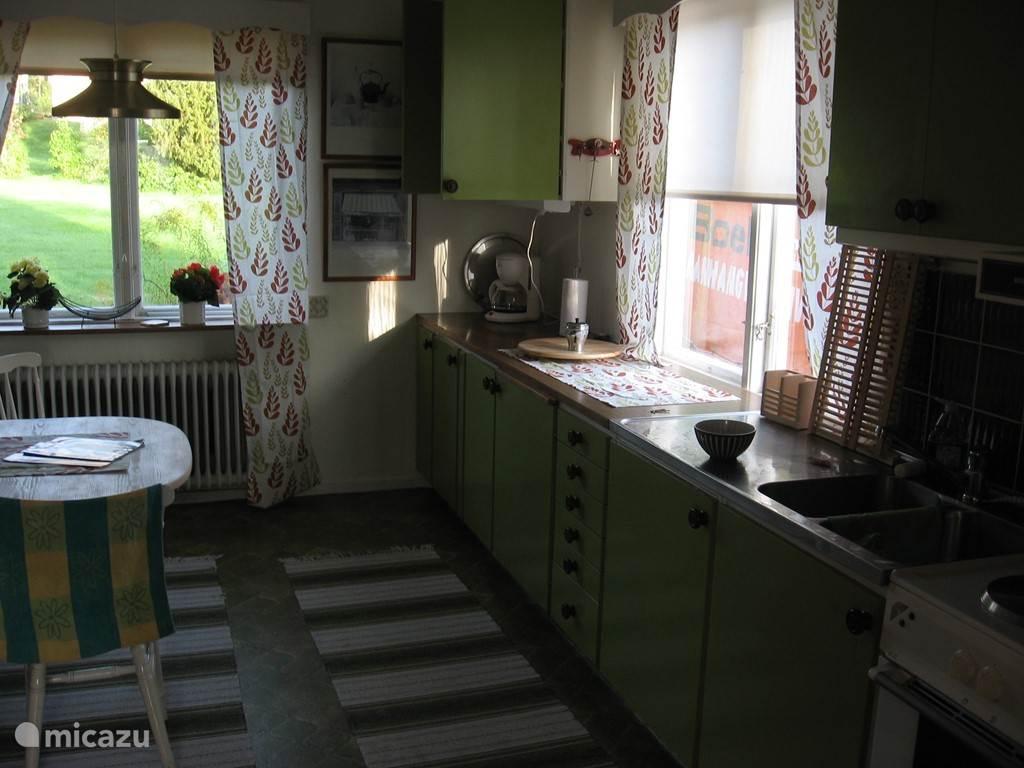 Gezellige keuken met uitzicht op de tuin en de mogelijkheid om met vier personen aan de tafel te ontbijten.