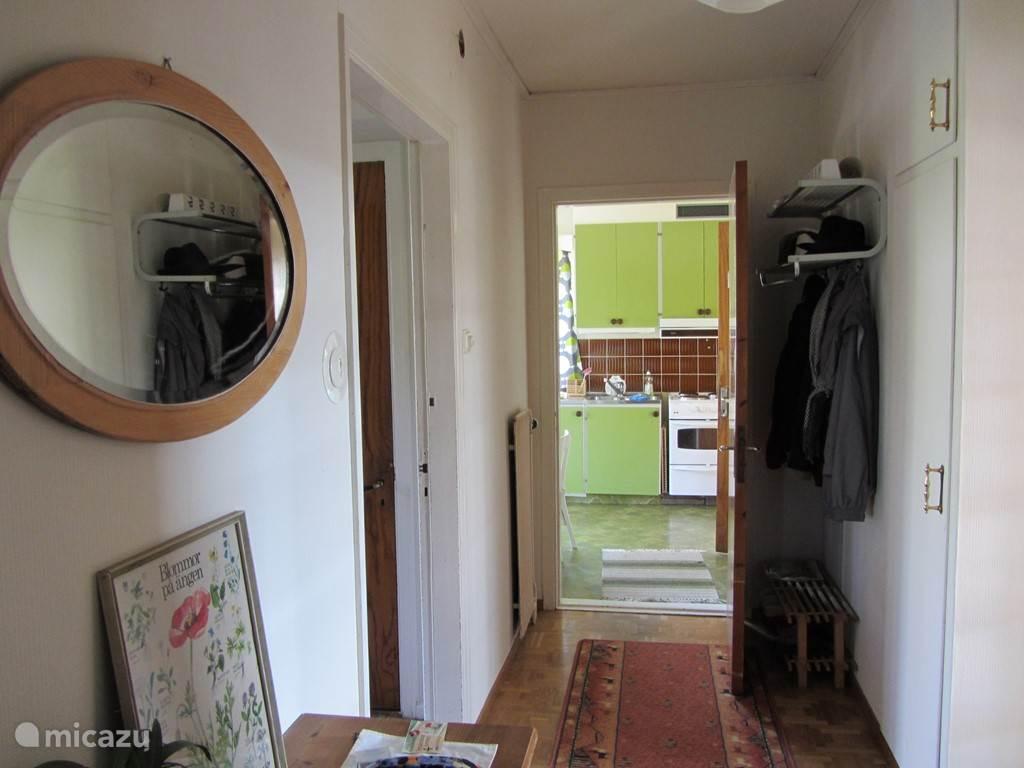 Hal. Aan het einde de keuken. Rechts de woonkamer. Links de hal met de voordeur, trap naar de eerste etage en de kelder.
