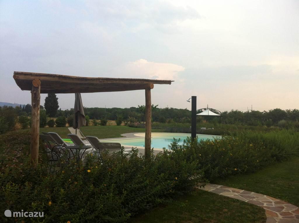 Mooi zwembad met overkapping, buitendouche en aparte badkamer met toilet bij het zwembad.