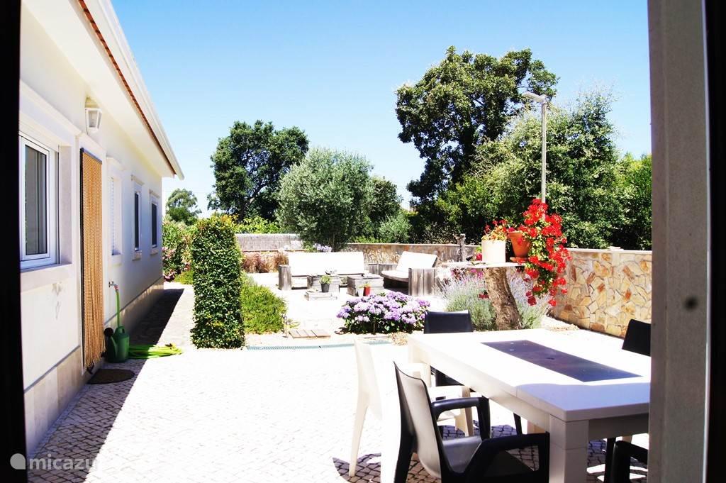 Tuin achter met drie terassen en een grote BBQ