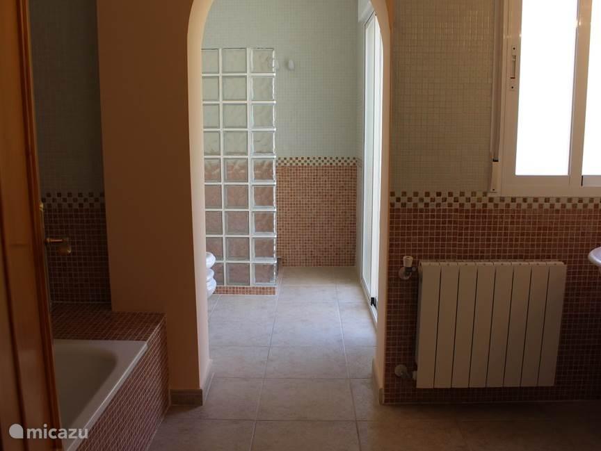 Grote badkamer behorende bij de masterbedroom met bad, toilet, bidet, douchehoek en dubbele wastafel.