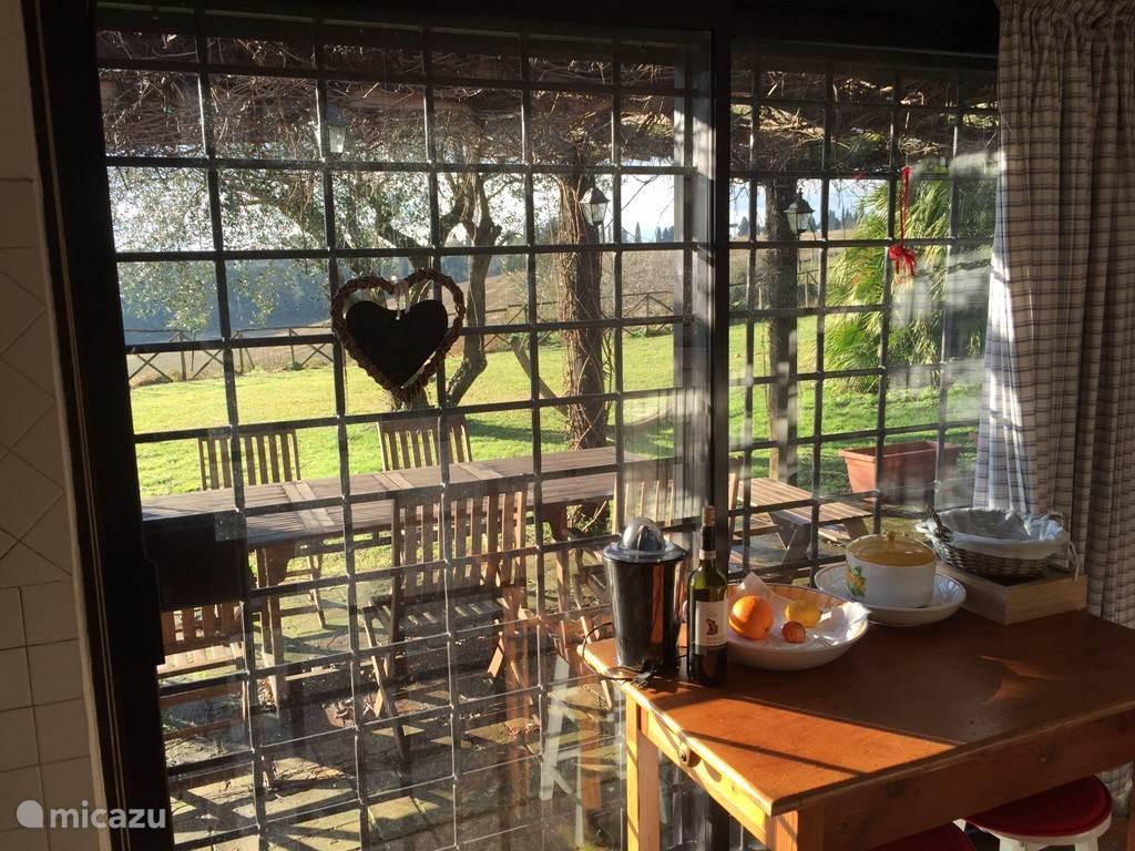 Keuken met open deur naar veranda/eethoek buiten