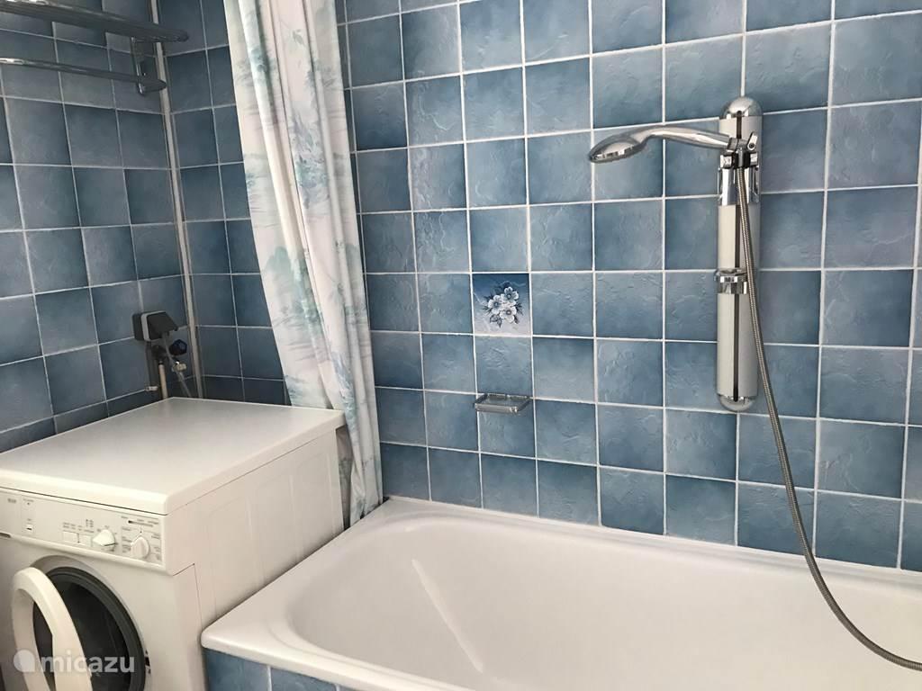 Badkamer  met bad, wasmachine  en Douche