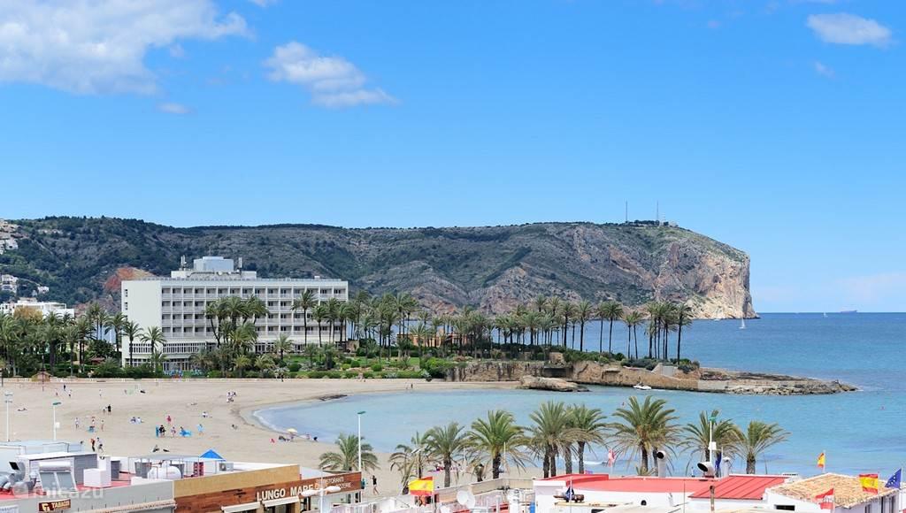 Het strand van Jávea met op de achtergrond het Parador hotel en de uitlopers van de bergrug Montgó.