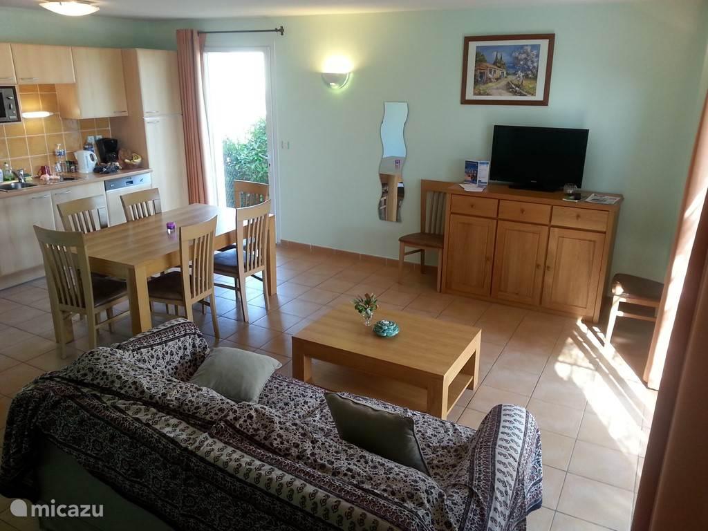 Woon- en eetkamer met keuken voorzien van alle apparatuur. De zitbank kan ook uitgetrokken worden om een tweepersoons bed van te maken.