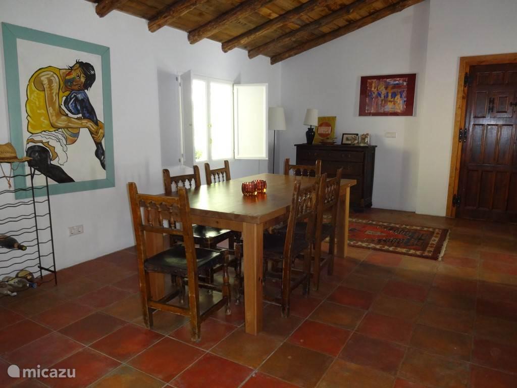 De huiskamer met comfortabele banken, een grote eettafel.