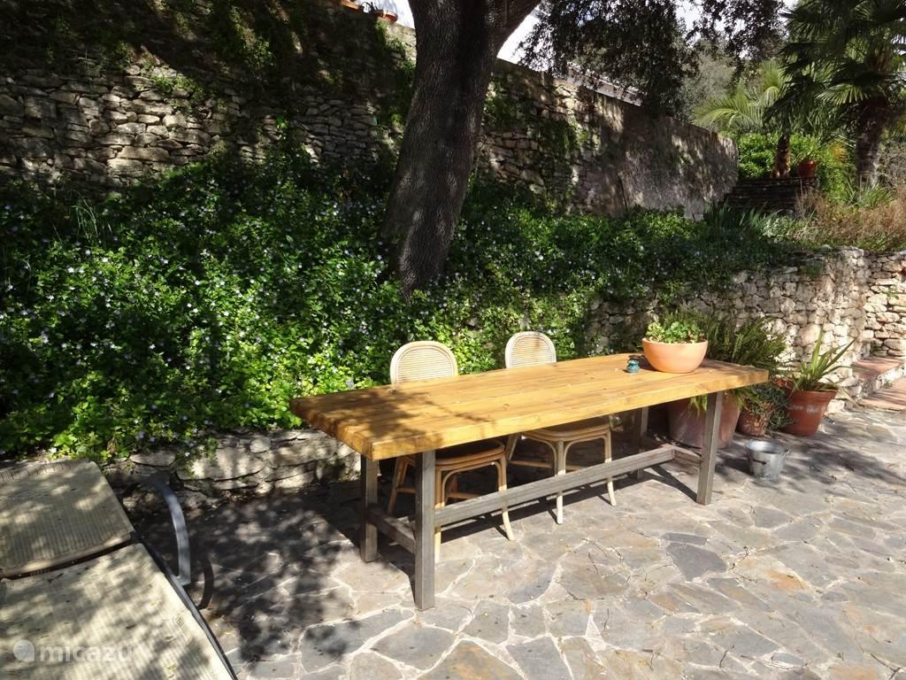 De stoere eettafel op het grote terras. Een plek in de schaduw. De plek om buiten te eten en de bbq aan te steken