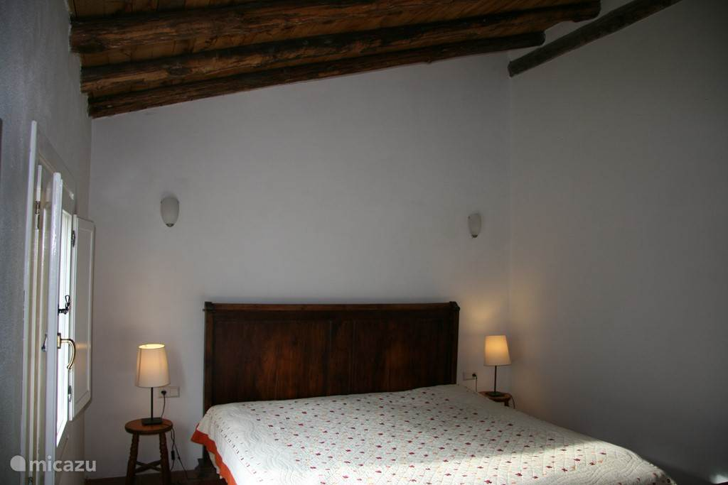 In de grote slaapkamer staat een groot kingsize bed met uitzicht op de vallei met bomen.