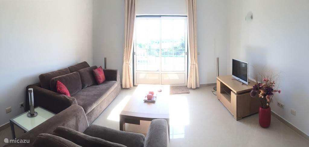 Het zit gedeelte van de huiskamer met airco en balkon, satelliet tv en een comfortabele slaapbank