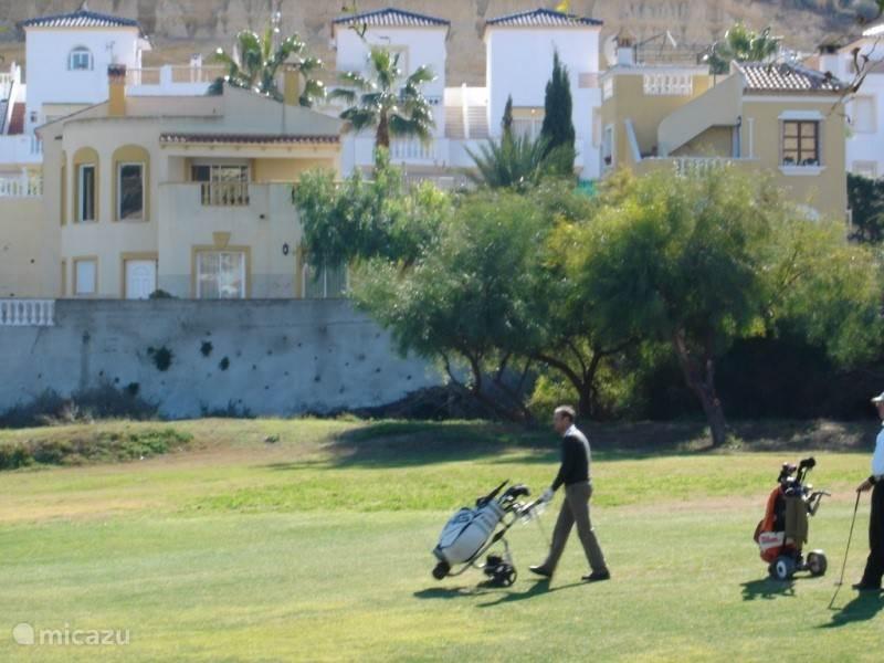 De woning vanaf de golfbaan met een golfspeler
