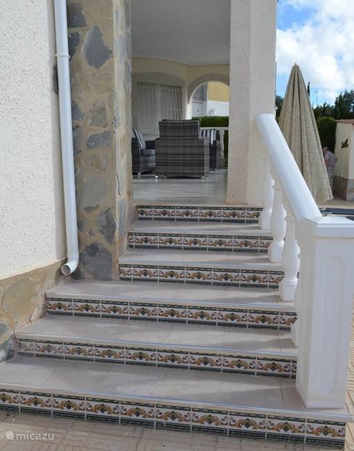Het overdekte terras/veranda ligt hoger dan de tuin en het zwembad.
