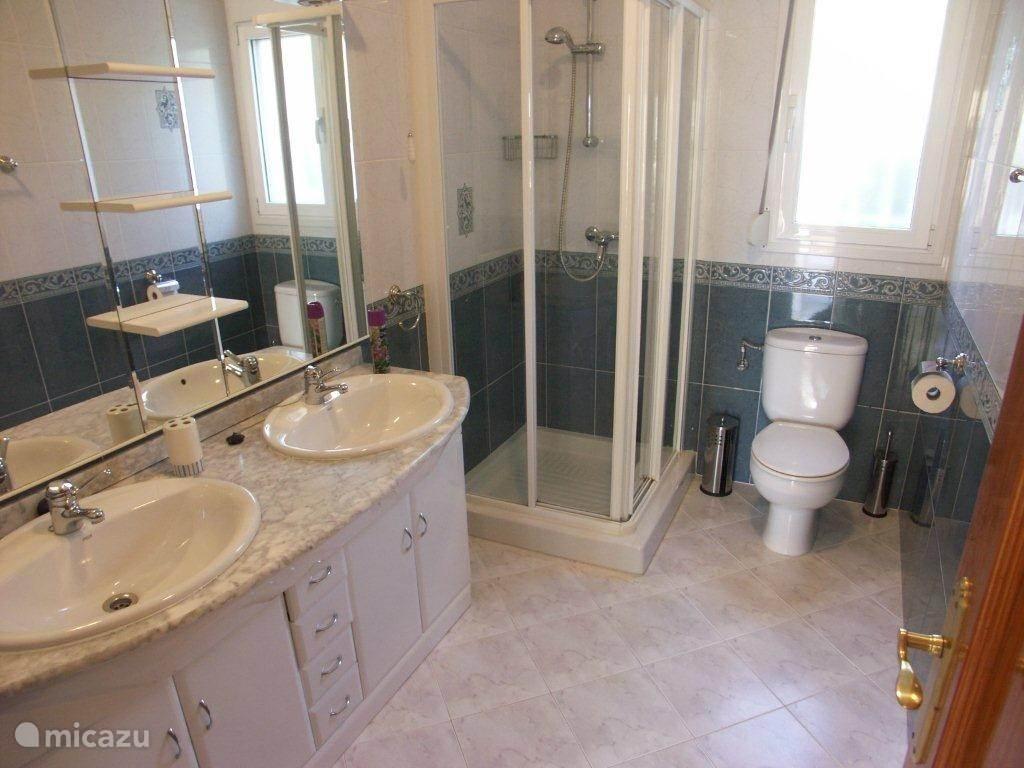 De badkamer met toilet, dubbele wastafel en douche.