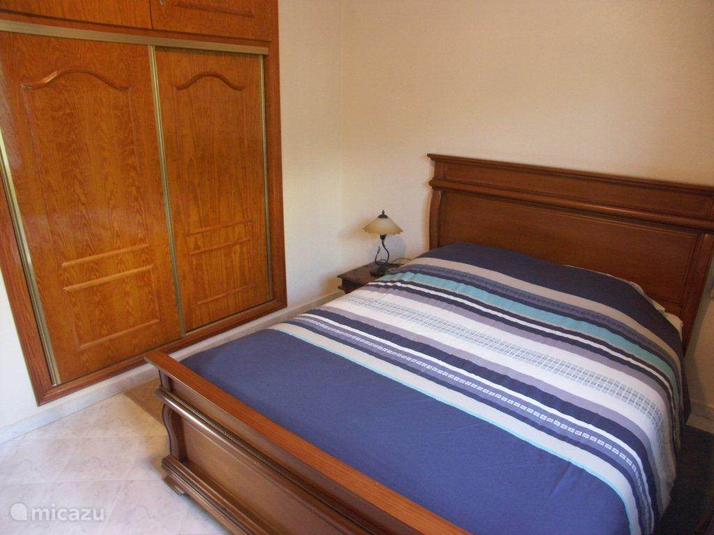 Slaapkamer één met inbouwkasten.