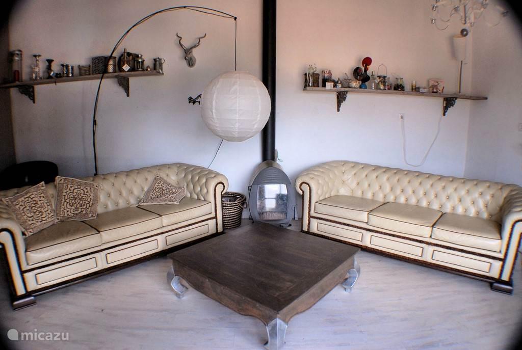 Woonkamer met houtkachel voor de wintermaanden. (2 slaapkamer appartement)