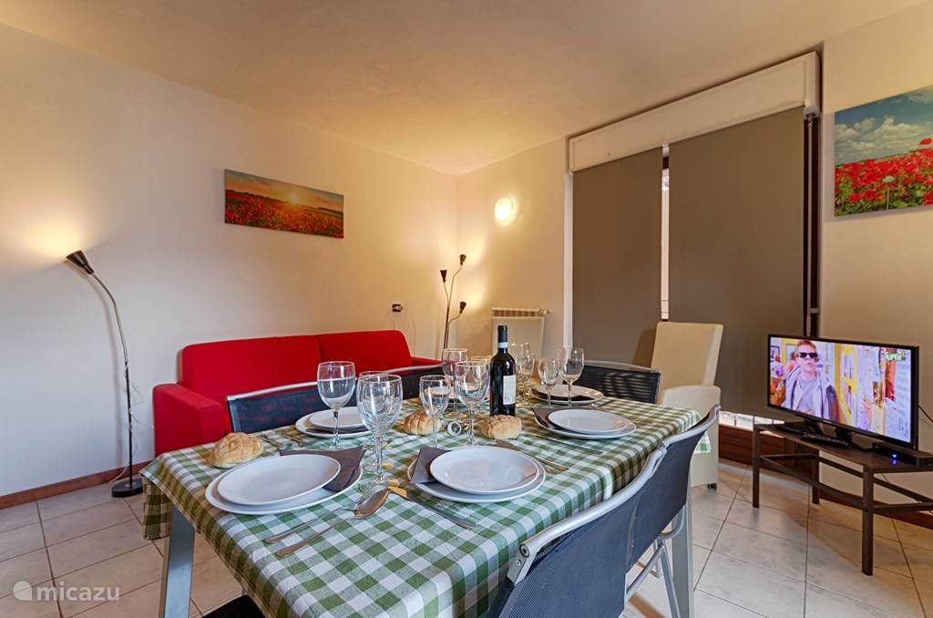 De woonkamer met de eettafel en de slaapbank.
