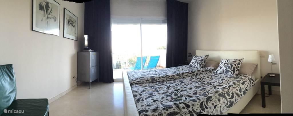 Master bedroom met tv aan het balkon