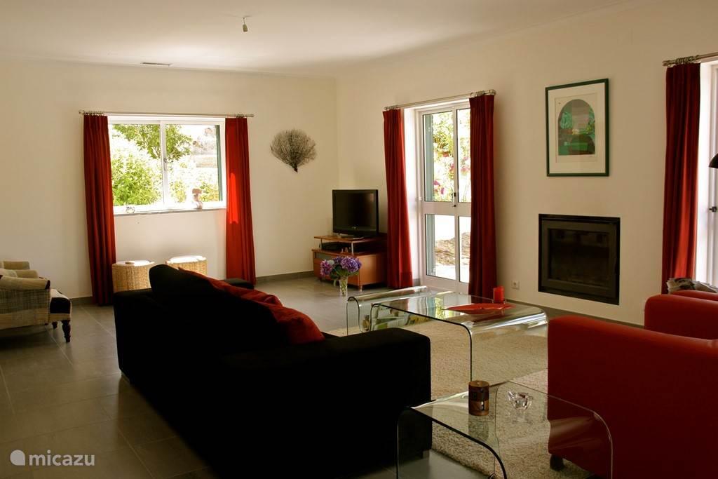 Modern ingerichte woonkamer met TV, een houtkachel en een prachtig uitzicht op de natuur. Wifi aanwezig.