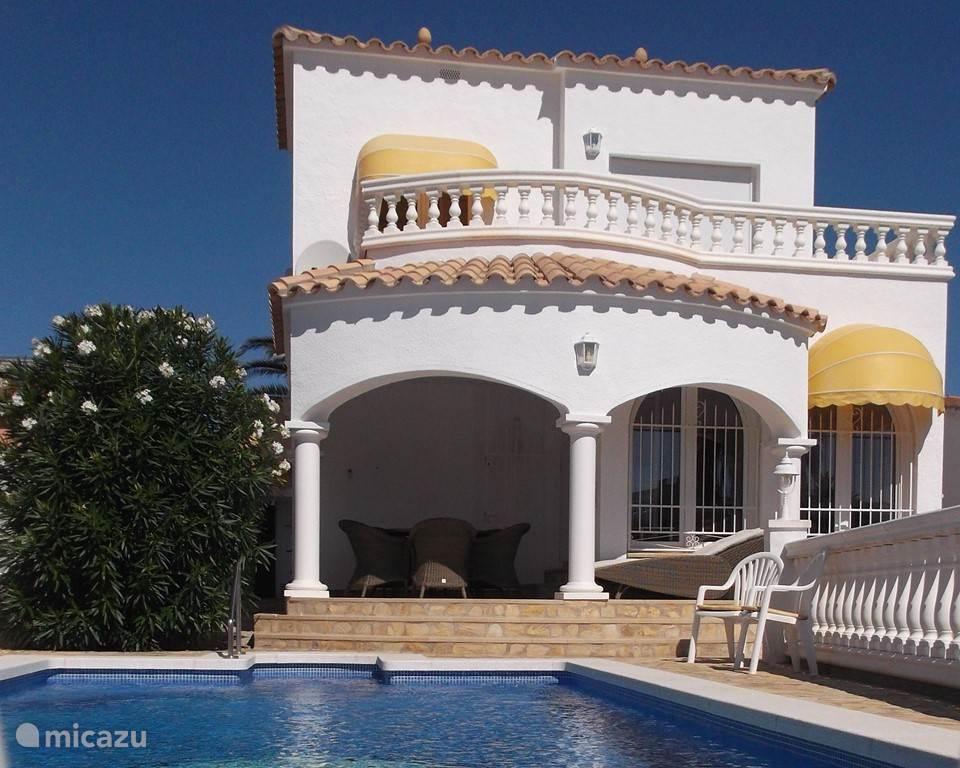 Foto van het prive zwembad met aanzicht achterkant van de villa.