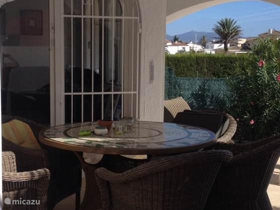 Aanzicht van het overdekte terras bij het zwembad en toegang tot de woonkamer.