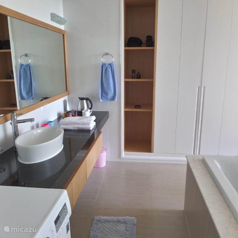 badkamer met douche, bad, toilet en wasmachine