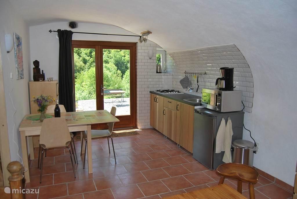 De keuken en het eetgedeelte; door de voordeur kijkt u uit op het terras.