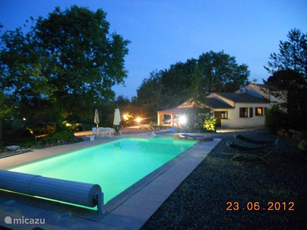 zwembad bij nacht met verlichte tuin