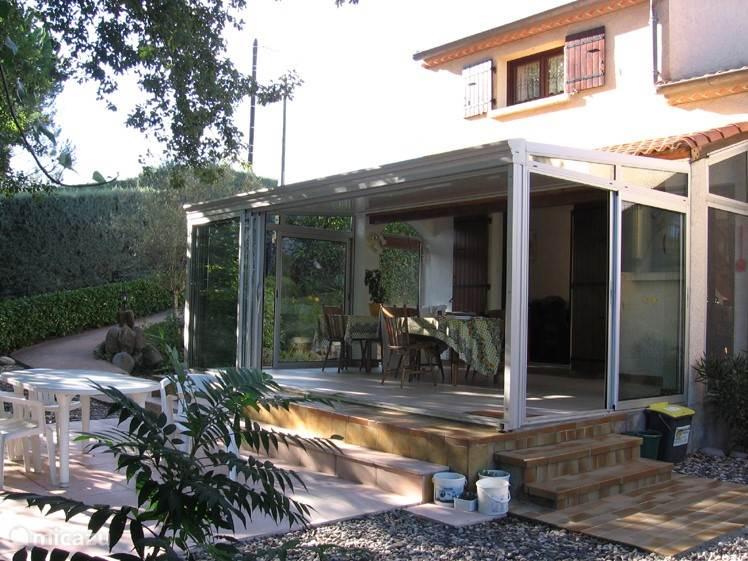 zuid-gerichte veranda met open deuren en terasje met tafel en stoelen