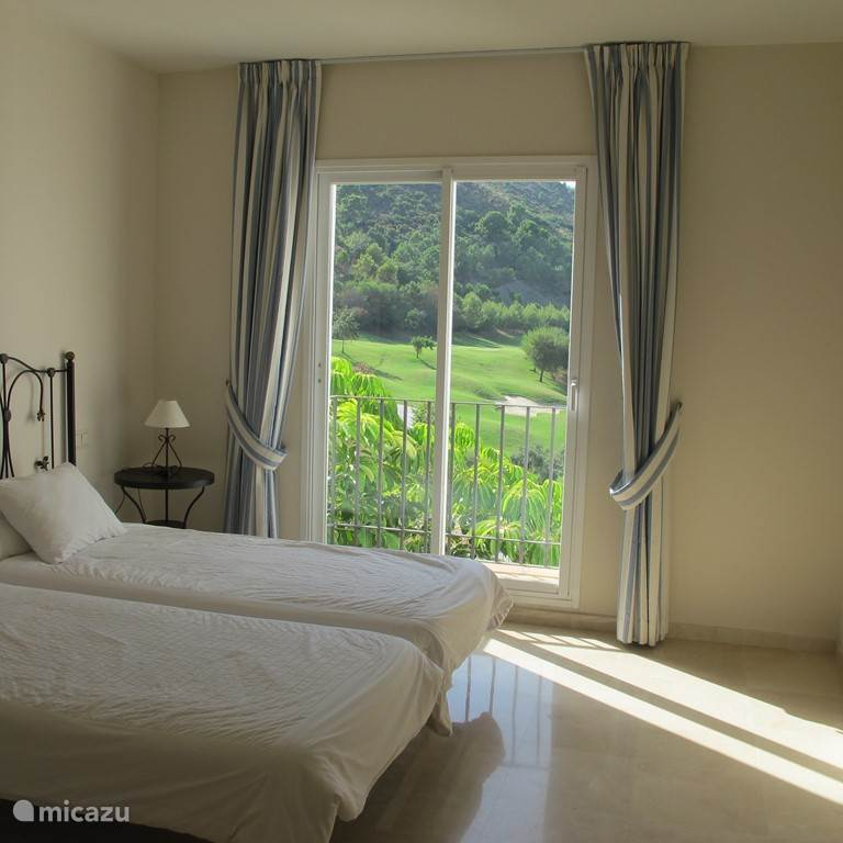 Second bedroom downstairs (3th floor) with french balcony and views to the hills and golfcourse.