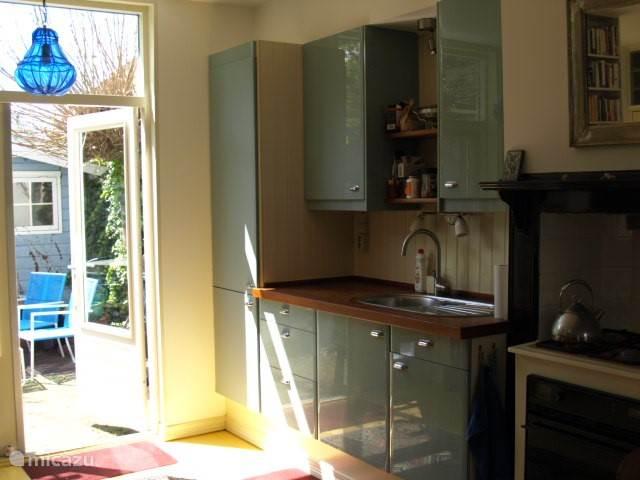 Open keuken, klein maar praktisch, met openslaande deuren naar de tuin. Afwassen gaat hier met de hand.