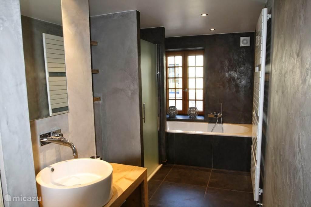 Badkamer met lavabo, douche en groot bad