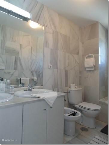 En Suite badkamer in marmer met bad/douche.