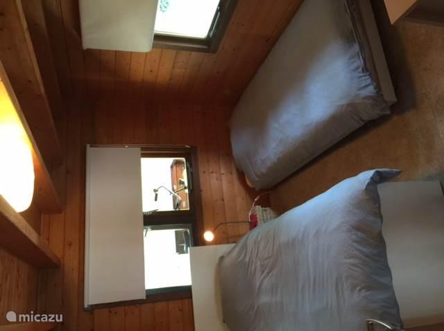Slaapkamer 1 op de begane grond heeft een 1-persoonsbed met een 1-persoons onderbed op wieltjes.