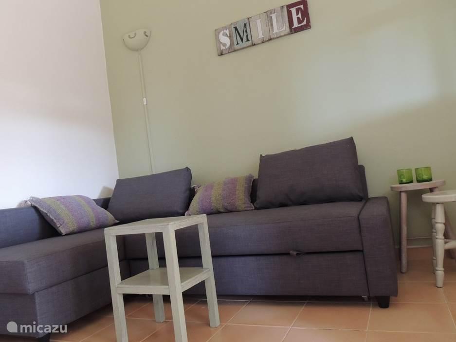 De zitkamer met slaapbank in appartement Quinta