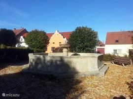 De fontein op het dorpsplein vlak voor de deur, er staan verschillende standbeelden, bankjes om te zitten en een netjes onderhouden plantsoen.