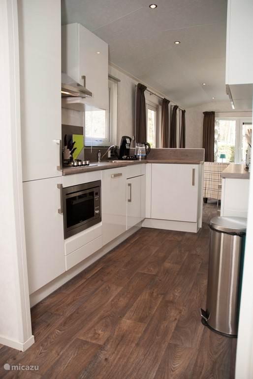 Keuken met gaskookplaat, afzuigkap, combi oven met magnetron, ruime koelkast met daaronder separate vriezer met 3 laden.
