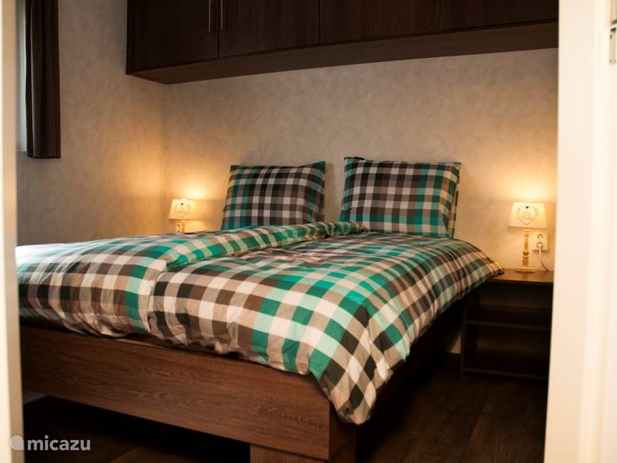 Master bedroom met comfortabele bedden voorzien van traagschuim toppers, smaakvol ingericht en grote schuifdeur kast.