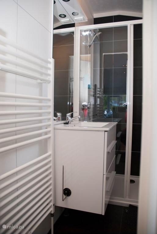Modern ingerichte, volledig betegelde badkamer met ruime douche gelegenheid voorzien van glazen schuifwand, badmeubel met twee laden en designradiator. Separaat WC duoblok. Mechanische ventilatie zowel als draai/kiep raam voor heerlijke frisse lucht.