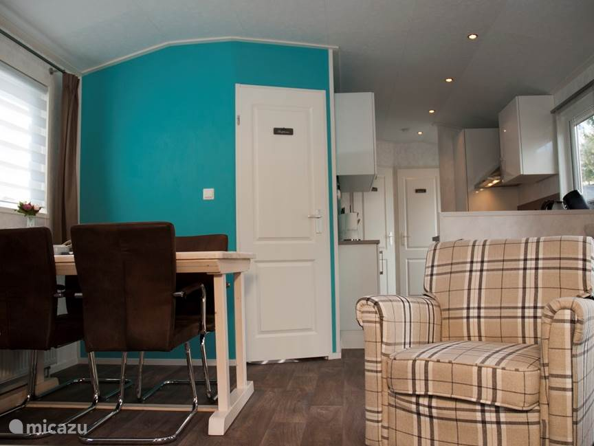Uitnodigend interieur met sfeervolle kleuren! Twee en een half zits bank, 2 fauteuils en eethoek met 4 stoelen.