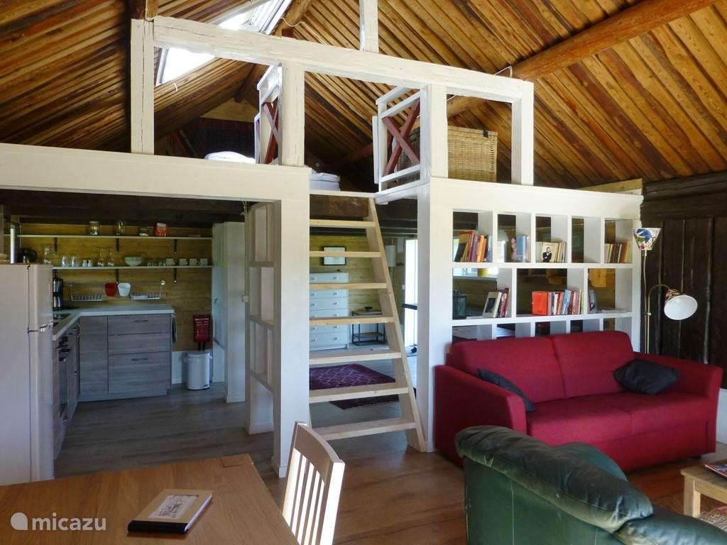 Vanaf entree blik op de woonkamer. De boekenkasten hebben we gemaakt van de oorspronkelijke staldeuren. Het gezellige interieur is met gevoel voor detail samengesteld. Je voelt je er meteen thuis, zeggen onze gasten.