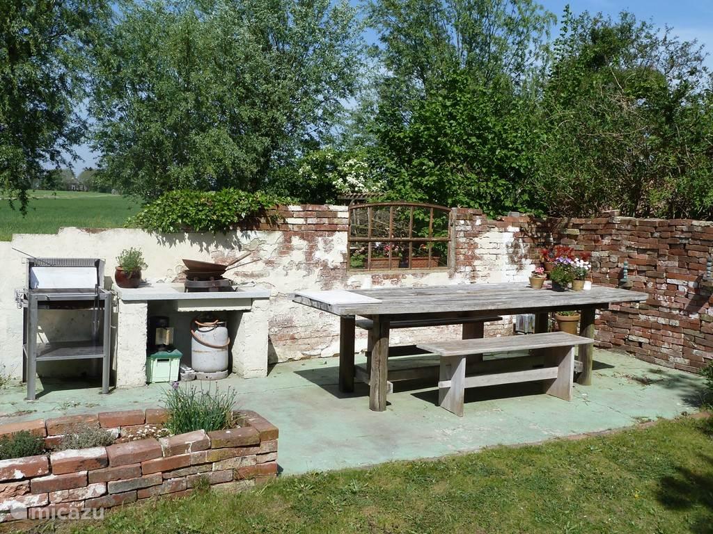 De tuin heeft een grote eettafel en barbecue