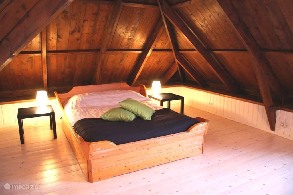 Slaapkamer met 2 persoons bed en wasbak
