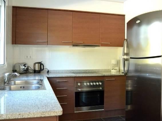 Keuken met grote koelkast, oven, afwasmachine, koffiezet apparaat , waterkoker en toaster