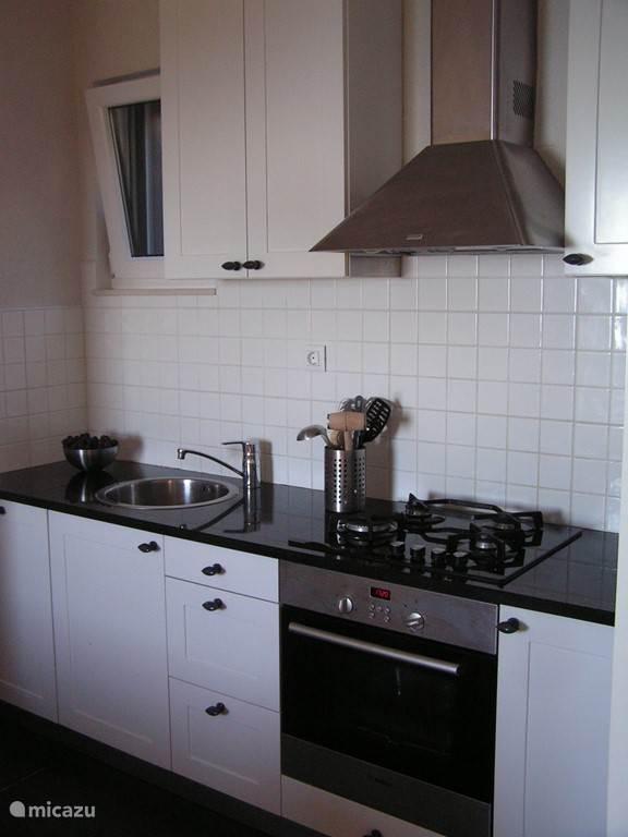 Ruime open keuken voorzien van magnetron, vaatwasser, oven, koelvriescombinatie, koffiezetapparaat en waterkoker