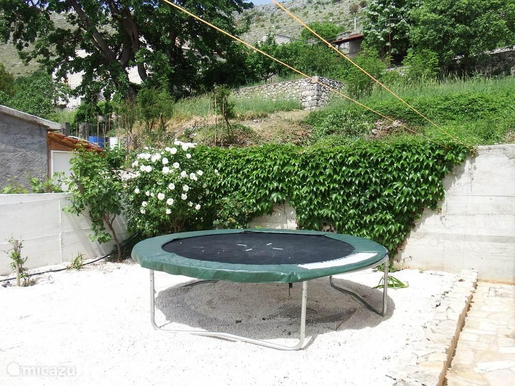 Voor de kinderen staat in de tuin een trampoline