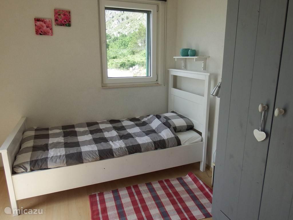 De tweede slaapkamer in ons huis heeft twee eenpersoonsbedden en grenst aan een fijn balkon met natuurlijk een mooi uitzicht op de Adriatische zee.