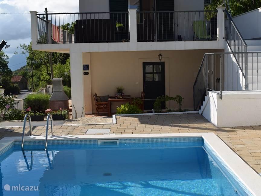 Het grote overdekte terras kijkt uit op het zwembad.