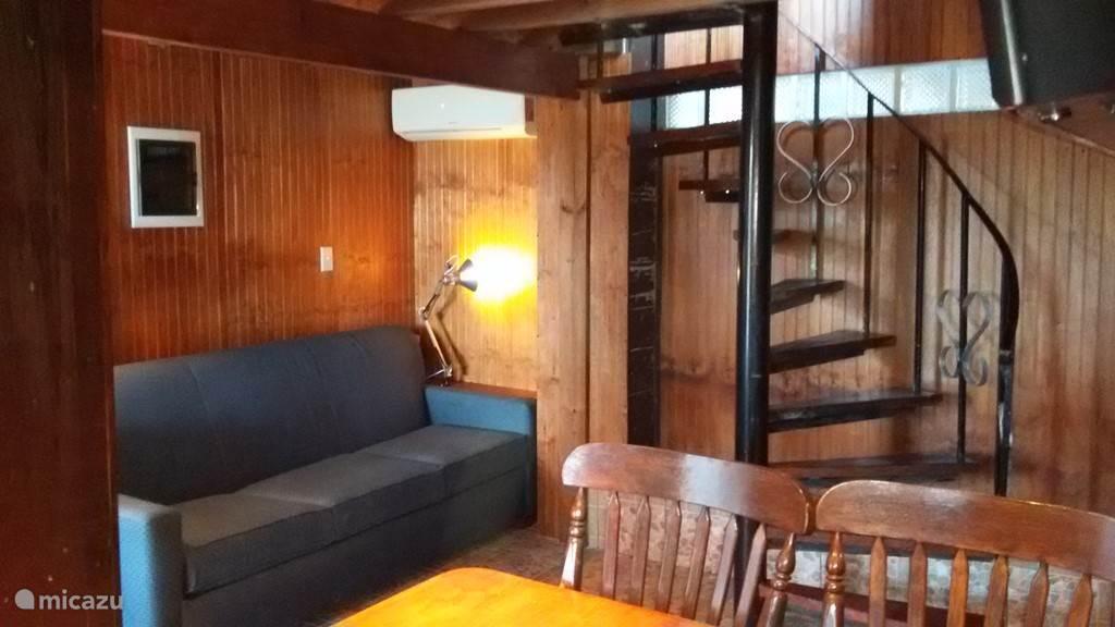 De wooneetkeuken. Draaitrap naar bovenverdieping. Slaapsofa met queensize bed.